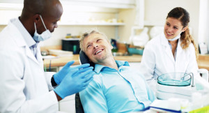 Dentist and assistant talking to patient in the chair