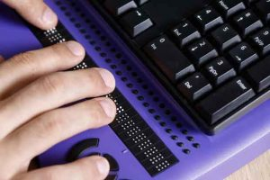 Blind person using computer with braille keyboard